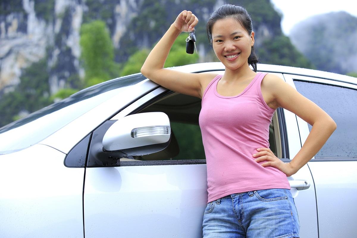 Joven mostrando las llaves de su auto nuevo que se encuentra detrás de ella.
