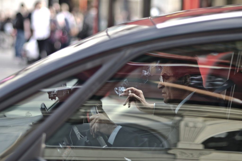 hombre fumando manejando su auto