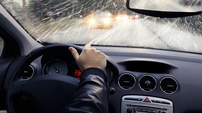 hombre conduciendo auto bajo la lluvia