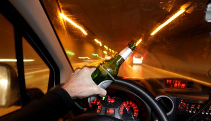 Hombre al volante con botella de cerveza